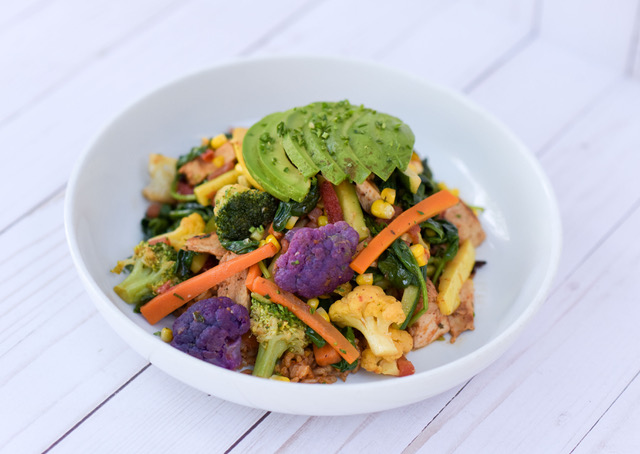 Photo of Cafe Vida's Veggie Bowl, which includes purple cauliflower, broccoli, carrots, corn, and avocado. Dish is presented on a white plate against a white background.